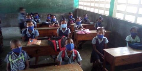 Haitian students physically distanced and wearing masks at school desks