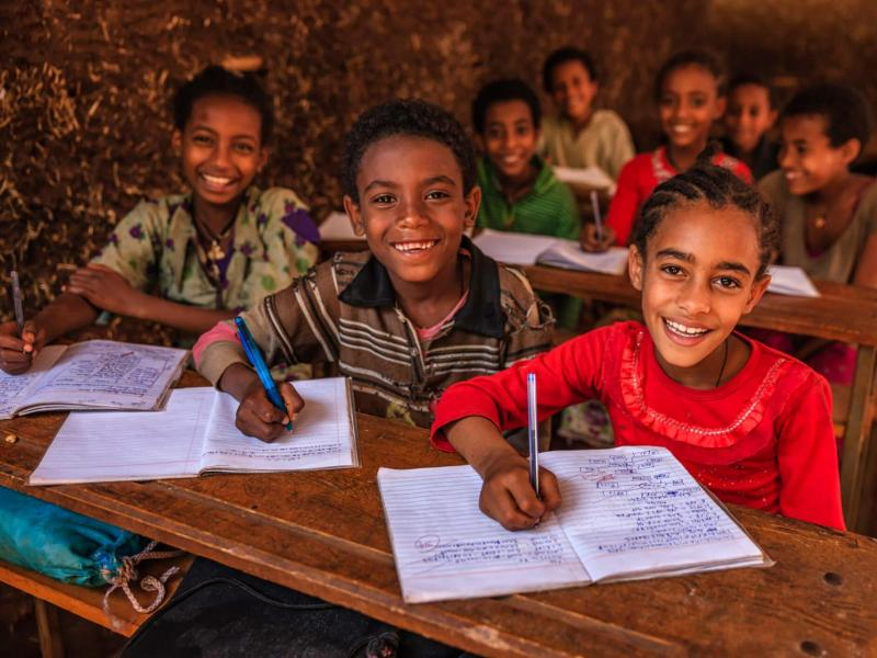 Children at desks for USAID SHARE